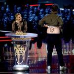 Кристен Белл (слева) смотрит как Сет Роген демонстрирует поддельную татуировку Вина Дизеля, вручив награду за лучшее комедийное выступление на церемонии вручения наград MTV Movie and TV Awards в Ангаре Баркера в Санта-Монике. Калифорния, 16 июня 2018 года