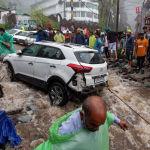 Люди пытаются вытащить автомобиль, поврежденный во время внезапных наводнений после сильных муссонных дождей в Бхагсунаге (Индия). 12 июля 2021 года