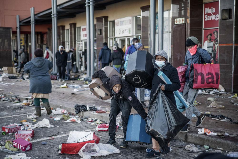 Мародеры забирают вещи в разрушенном торговом центре в Вослоорусе (ЮАР). 14 июля 2021 года