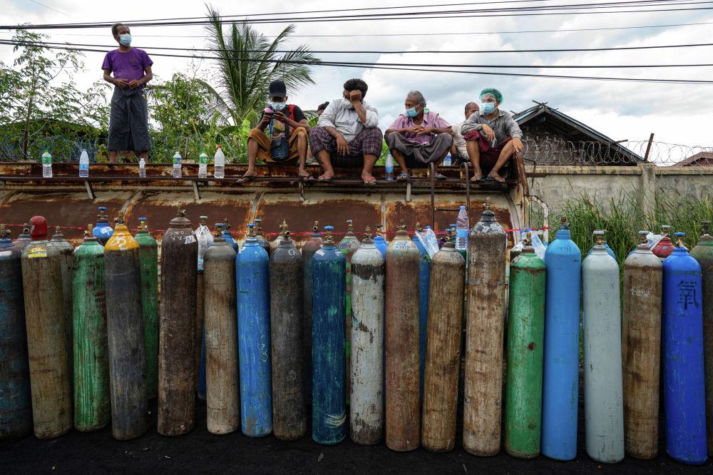Люди, ожидающие наполнения пустых кислородных баллонов возле завода в Мандалае (Мьянма). 13 июля 2021 года