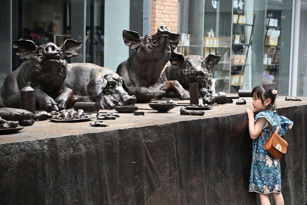 Девочка смотрит на статуи свиней возле художественного музея в Пекине.
