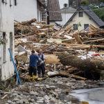 Двое мужчин пытаются забрать товары рядом с обломками домов, разрушенных наводнением в Шульде недалеко от Бад-Нойенара, западная Германия, 15 июля 2021 года.