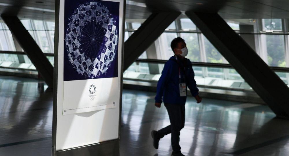 Мужчина в маске проходит мимо вывески Олимпийских игр 2020 года в Токио в главном пресс-центре. Архивное фото