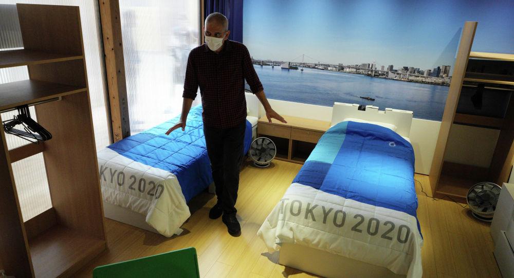 Журналист смотрит на картонные кровати для Олимпийских и Паралимпийских деревень Токио-2020, которые показаны в демонстрационном зале Village Plaza в Токио. 20 июня 2021 года