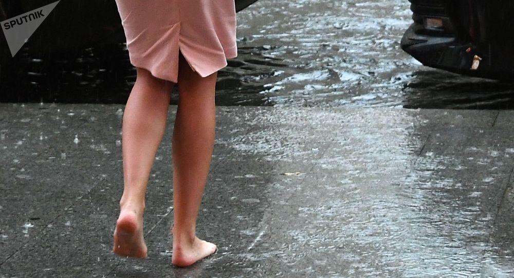 Девушка на одной из улиц города во время дождя. Архивное фото