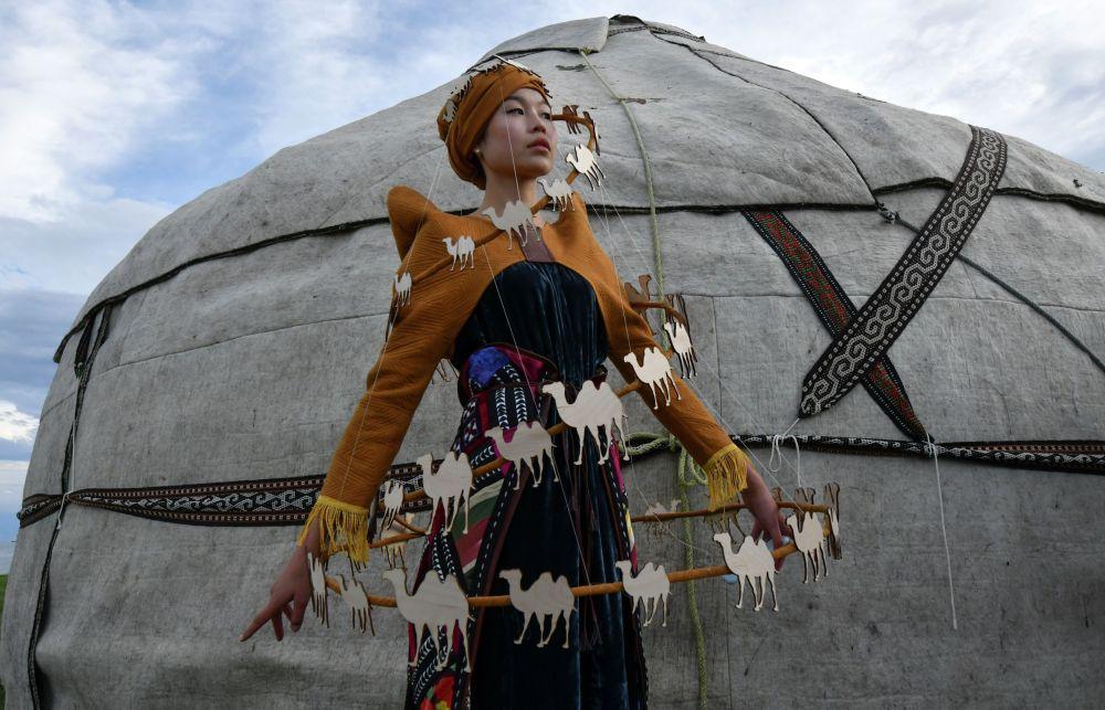Модель демонстрирует наряд из коллекции кыргызского дизайнера Чолпонай Алмаз Кызы во время Всемирного фестиваля моды кочевников Иссык-Куль 2021 в Чолпон-Ате
