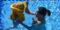 Девушка с ребёнком купаются в бассейне. Архивное фото