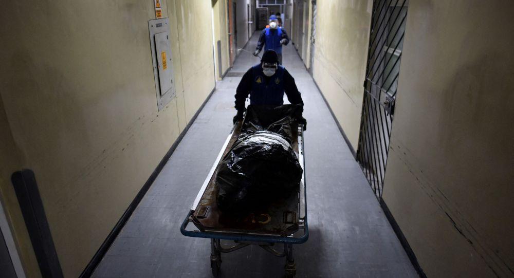 Медицинский персонал извлекает тело жертвы COVID-19