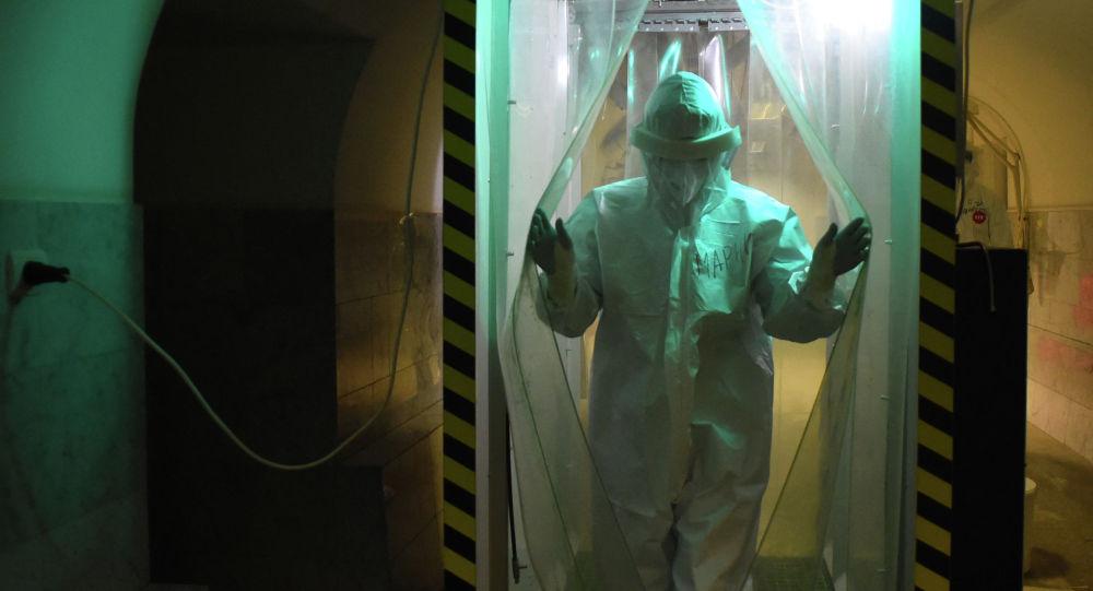 Медициналык кызматкер дезинфекциялоо кабина аркылуу өтүп жатат