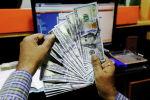 Трейдер показывает банкноты в долларах США в пункте обмена валюты в Карачи