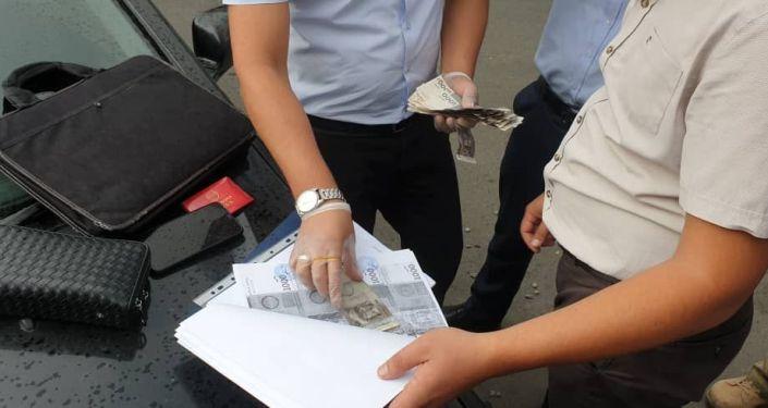Сверка купюр при задержании с поличным сотрудника ОВД Сокулукского района по факту вымогательства взятки. 22 июля 2021 года