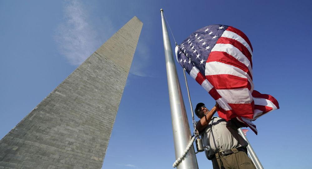 Сотрудник Службы национальных парков заменяет флаг у памятника Вашингтону, который открылся сегодня после шести месяцев закрытия из-за мер безопасности COVID-19 в Вашингтоне. США, 14 июля 2021 года