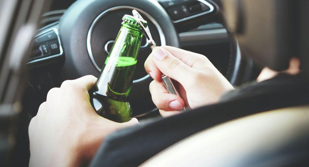 Водитель открывает алкогольный напиток за рулем автомобиля. Иллюстративное фото