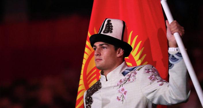 Знаменосец сборной Кыргызстана Денис Петрашов возглавляет делегацию во время парада спортсменов церемонии открытия Олимпийских игр 2020 года в Токио на Олимпийском стадионе в Токио. 23 июля 2021 года