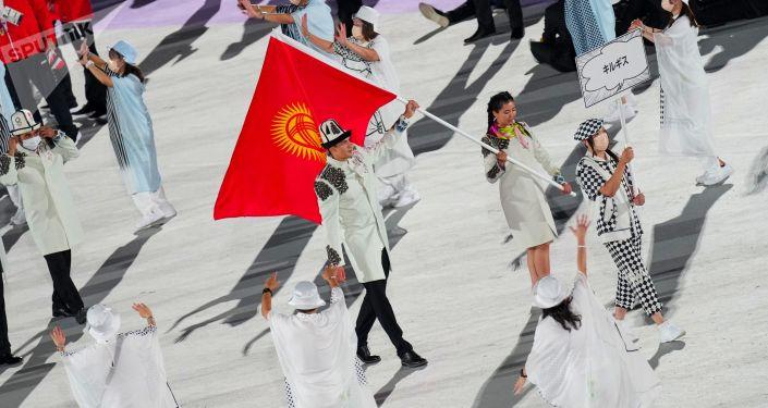 Знаменосцы сборной Кыргызстана участница соревнований по пулевой стрельбе Каныкей Кубанычбекова и пловец Денис Петрашов во время парада атлетов на церемонии открытия XXXII летних Олимпийских игр в Токио.