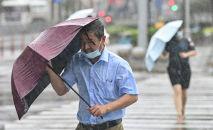Люди переходят улицу под ветром и дождем во время тайфуна