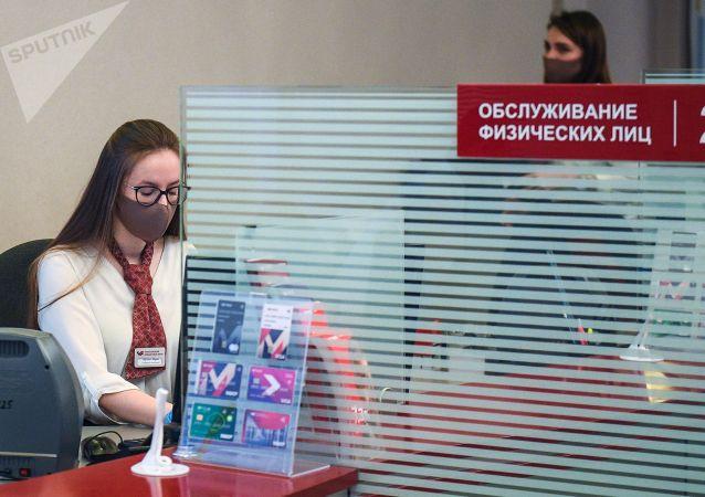 Сотрудница банка в защитной маске во время работы. Архивное фото
