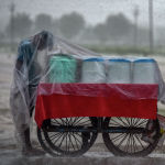 Индиянын Аллахабад аймагында көчө соодагери жаандан жашырынып жатат