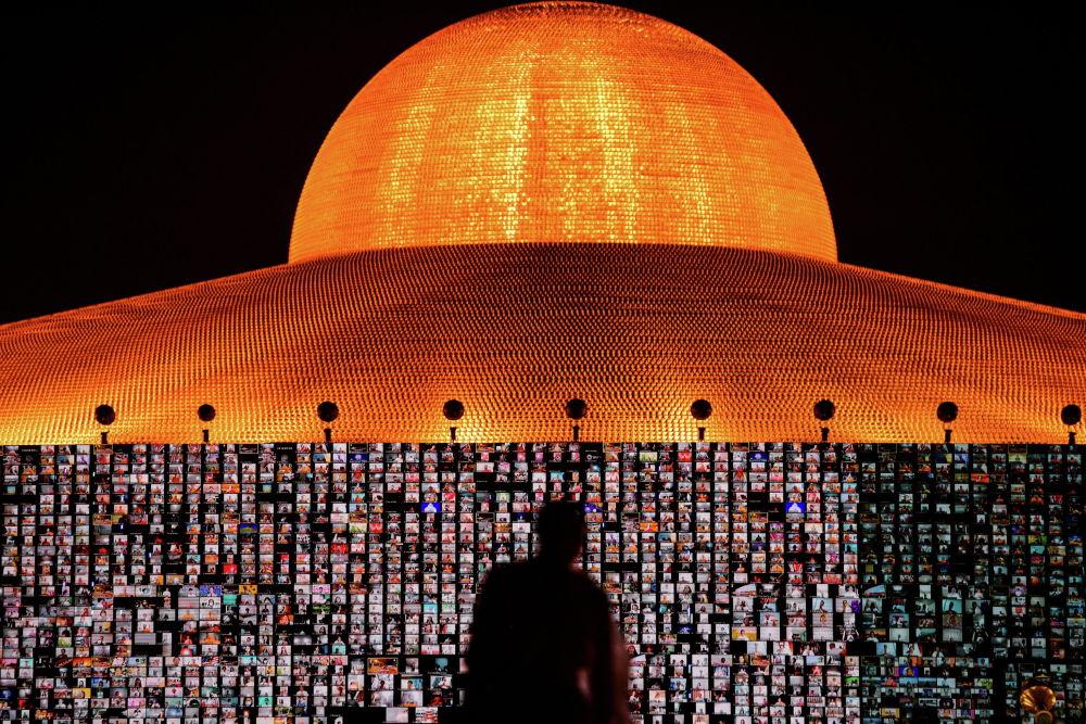 Таиланддын Ват Пхра Дхаммакая храмында Будда дининдегилердин күнүн белгилөө аземи учурунда адамдар Zoom тиркемеси аркылуу сыйынып жатканын экрандан көрсөтүп жатат