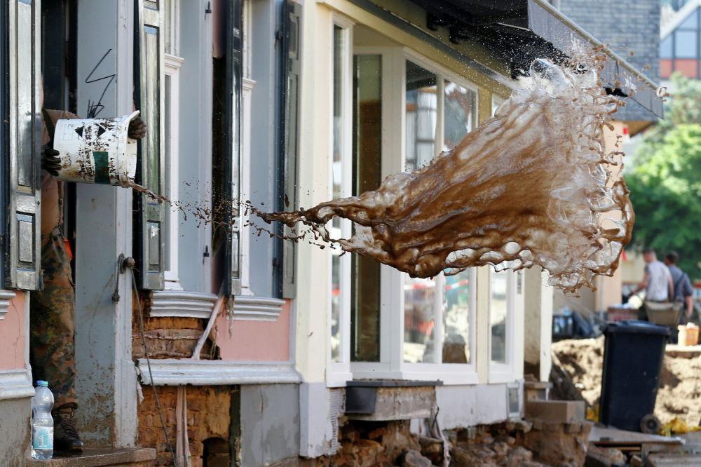 Германиянын Бад-Мюнстерайфел аймагында суу каптоодон кийин үйүн тазалап жаткан киши.