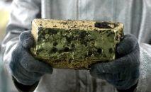 Сотрудник Таласского золоторудного комбината держит в руках слиток золота.
