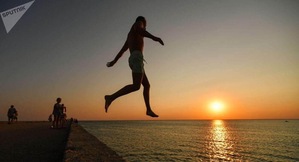 Мужчина прыгает с пирса. Архивное фото
