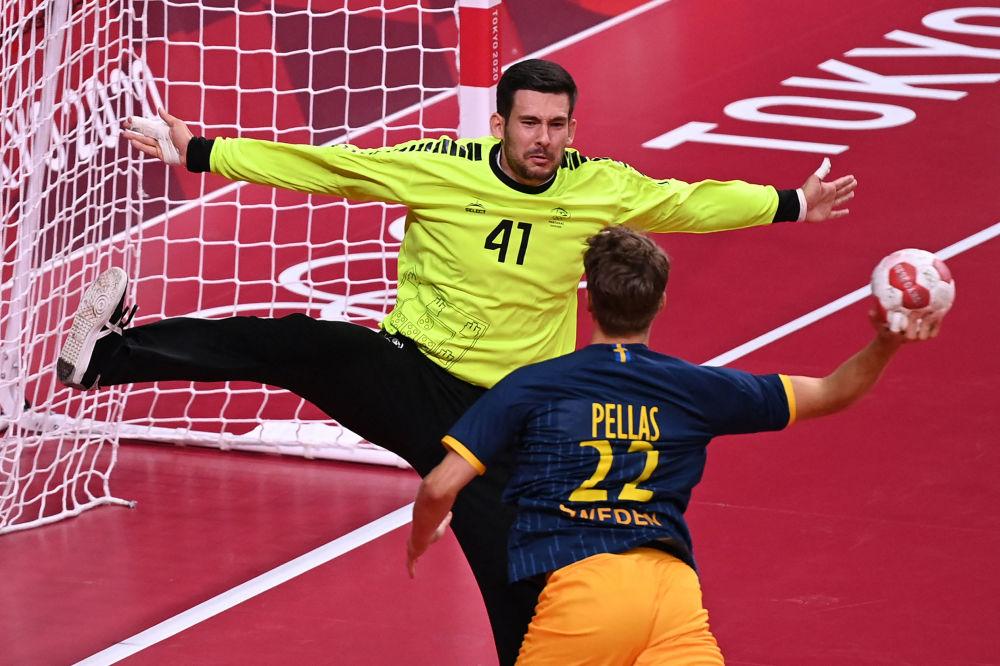 Вратарь Португалии Густаво Капдевиль и Лукас Пеллас из Швеции в борьбе за мяч во время гандбольного матча