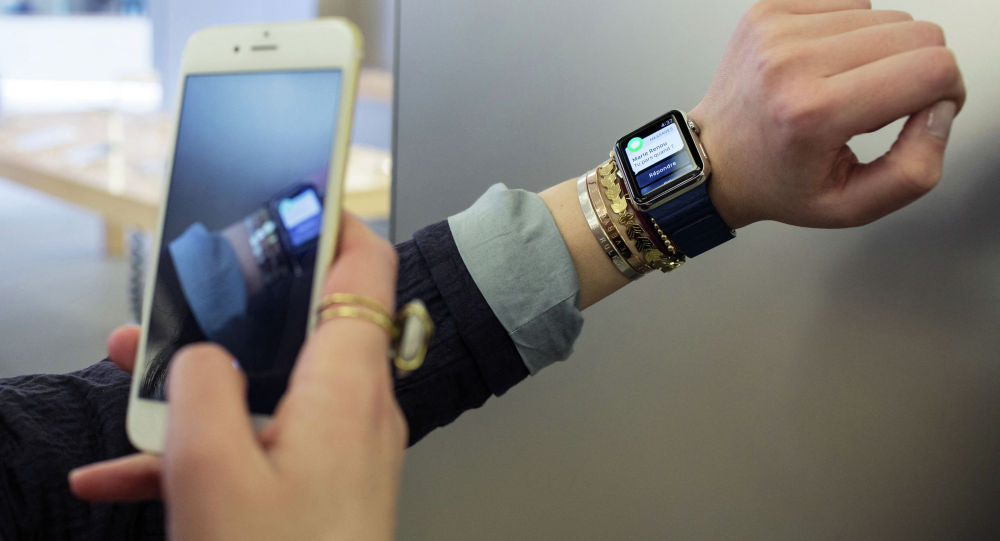 Девушка на iPhone фотографирует часы Apple Watch. Архивное фото