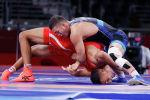 Акжол Махмудов (в синем) из Кыргызстана борется с Ламджедом Маафи из Туниса в весовой категории до 77 кг во время Олимпийских игр 2020 года в Токио. 2 августа 2021 года