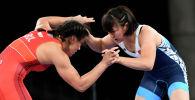 Кыргызстанка Мээрим Жуманазарова во время схватки с Мими Николова Христова из Болгарии в 1/8 финала Олимпийских игр в Токио. 1 августа 2021 года