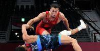 Акжол Махмудов (в красном) из Кыргызстана борется с Рафиком Гусейновым из Азербайджана в весовой категории до 77 кг во время Олимпийских игр 2020 года в Токио. 2 августа 2021 года