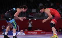 Кыргызстанка Айсулуу Тыныбекова (в синем) во время схватки с Анастасией Григорьевой из Латвии в весовой категории до 62 кг во время Олимпийских игр 2020 года в Токио. 3 августа 2021 года