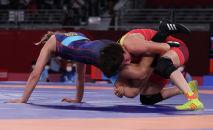 Кыргызстанка Айсулуу Тыныбекова (в красном) борется с румынкой Кристой Тунде Инкзе на четвертьфинале в весовой категории до 62 кг во время Олимпийских игр 2020 года в Токио. 3 августа 2021 года
