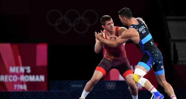 Акжол Махмудов из Кыргызстана во время схватки с Тамашом Лоринцем из Венгрии на финале Олимпийских игр в Токио. 2 августа 2021 года