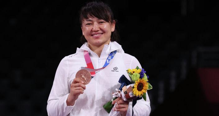 Бронзовая медалистка из Кыргызстана Мээрим Жуманазарова позирует со своей медалью после соревнований по вольной борьбе среди женщин в весовой категории до 68 кг на Олимпийских играх в Токио-2020. 03 августа 2021 года