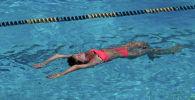 Девушка плавает в бассейне. Архивное фото