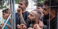 Мигранты у забора в лагере беженцев на военном полигоне Руднинкай, к югу от Вильнюса (Литва)