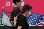 Женщины в масках проходят мимо рекламного щита с американским флагом и статуей Свободы