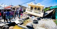 Талкаланган үйлөр, уранды алдынан табылган кишилер. Гаитидеги зилзаладан 12 сүрөт