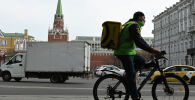 Сотрудник курьерской службы едет на велосипеде по улице в Москве. Архивное фото