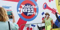 Посетители фотографируются у баннера с символикой международного джазового фестиваля Koktebel Jazz Party-2021.