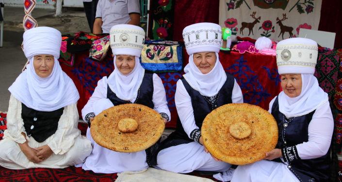 Женщины в национальных одеждах на фестивале мастеров и дизайнеров Золотая долина в городе Джалал-Абад