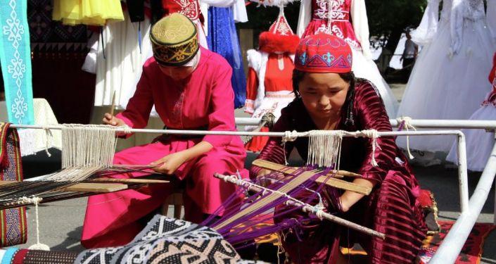 Девочки в национальных одеждах на фестивале мастеров и дизайнеров Золотая долина в городе Джалал-Абад