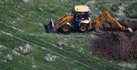 Траншея казып жаткан трактор. Архив