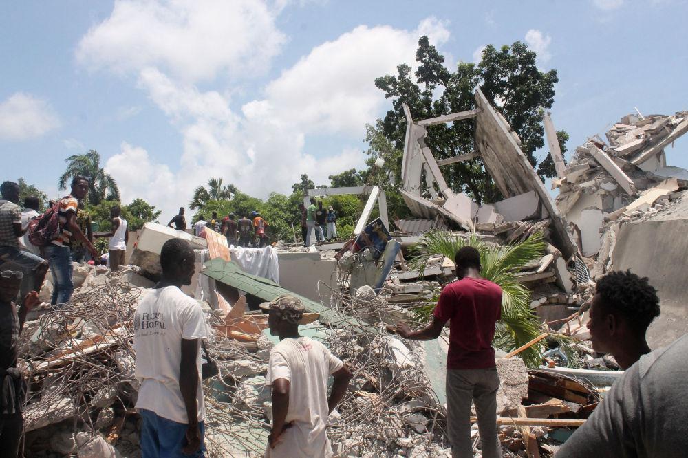 Люди у здания отеля на Гаити разрушенного сильным землетрясением. 14 августа 2021 года