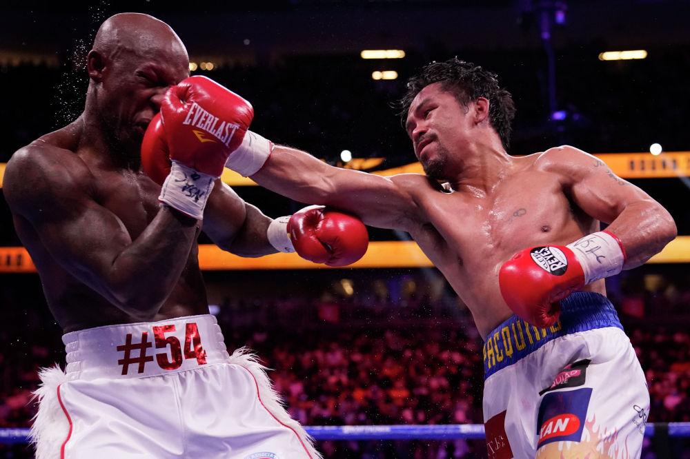 Филиппинский боксер Мэнни Пакьяо наносит удар кубинцу Йорденису Угасу в бое за звание чемпиона мира в полусреднем весе по версии Всемирной боксерской ассоциации (WBA) в в Лас-Вегасе. 21 августа 2021 года