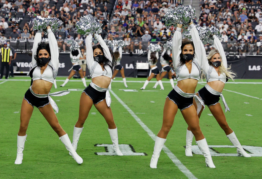 Девушки из группы поддержки Las Vegas Raiderettes выступают во время предсезонной игры против Seattle Seahawks. 14 августа 2021 года