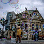 Мальчик играет с мыльными пузырями перед зданием Старой оперы во Франкфурте, Германия. 17 августа 2021 года