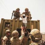 Коалиционные силы Великобритании, Турции и США помогают ребенку во время эвакуации в аэропорту Кабула, Афганистан. 20 августа 2021 года
