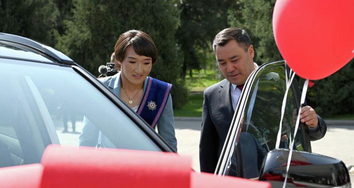 Президент Садыр Жапаров показывает автомобиль марки Toyota Rav 4 серебряной медалистке Олимпийских игр в Токио Айсулуу Тыныбековой на торжественной церемонии вручения Токио в госрезиденции Ала-Арча. 23 августа 2021 года